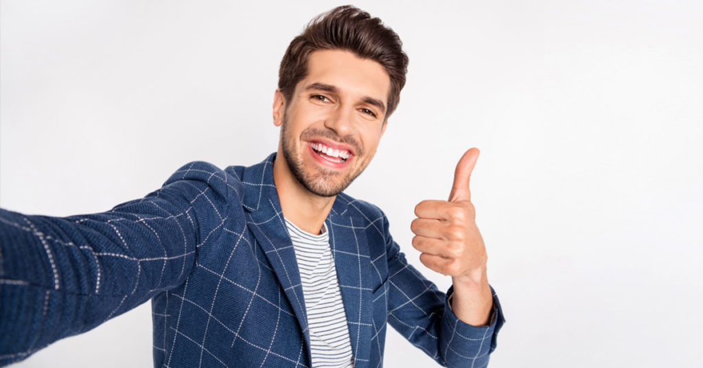 happy smiling man with full head of hair giving a thumbs up